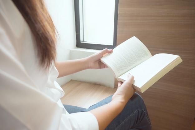 Vrouwen lezen boek en ontspannen in de bibliotheek. selectieve focus