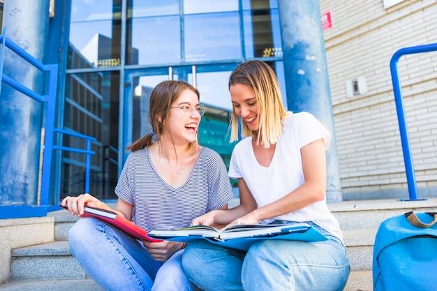 Vrouwen lezen leerboek en lachen