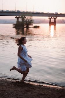 Vrouwen lopen langs het strand bij zonsondergang levensstijl fulllength portret van een gelukkige jonge vrouw in een w...