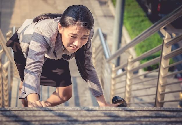Vrouwen lopen met blote voeten de ladder op en houden zwarte hoge hakken met vermoeidheid vast