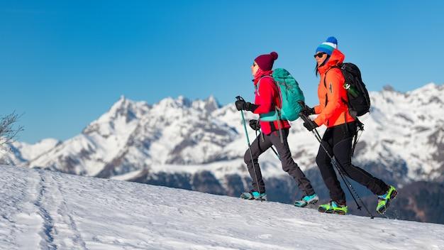 Vrouwen lopen met stijgijzers in de sneeuw in de bergen