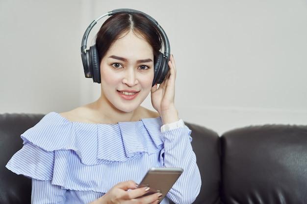 Vrouwen luisteren naar muziek via een zwarte koptelefoon. in een comfortabele en goede stemming.