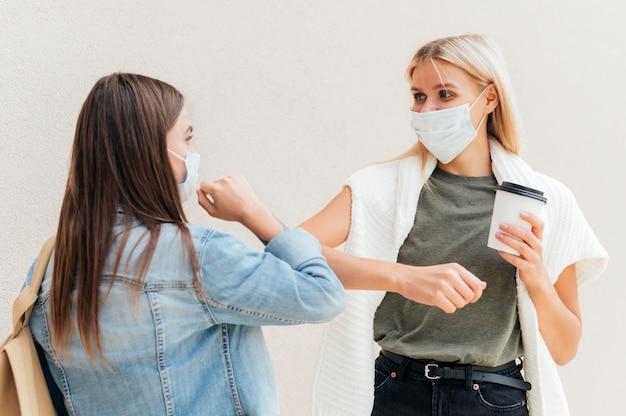 Vrouwen maken elleboogbulten met sociale afstandelijkheid