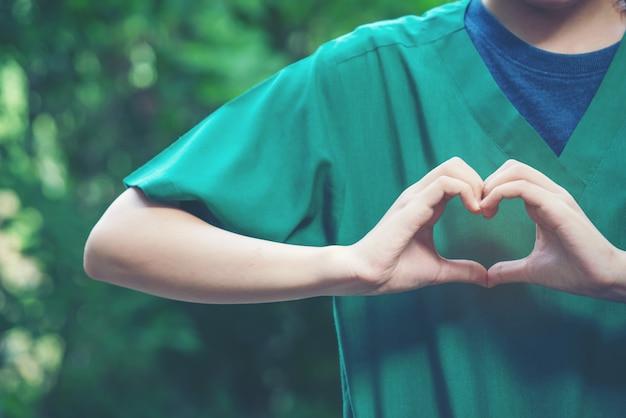 Vrouwen maken hartvormen met hun handen