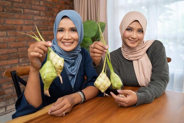 Vrouwen maken thuis traditioneel ketupat-voedsel voor eid-feesten
