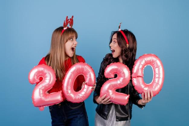 Vrouwen met 2020 nieuwe jaarballons die grappige die kerstmishoepels dragen over blauw worden geïsoleerd