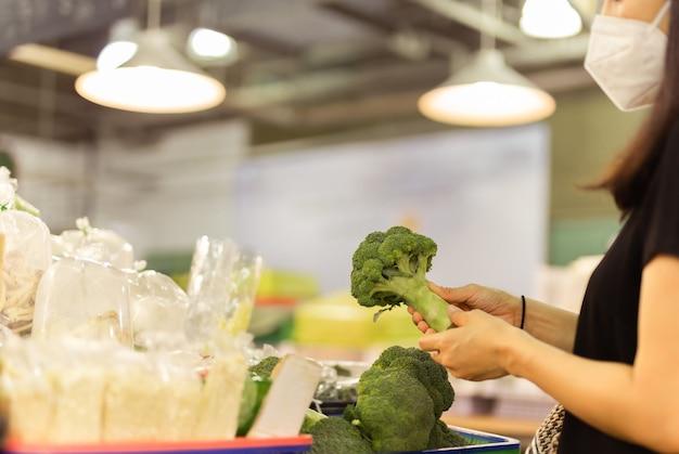 Vrouwen met beschermend masker halen broccoli op in groentewinkel