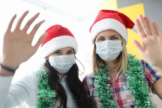 Vrouwen met beschermende medische maskers en kerstmanhoeden die naar de camera zwaaien