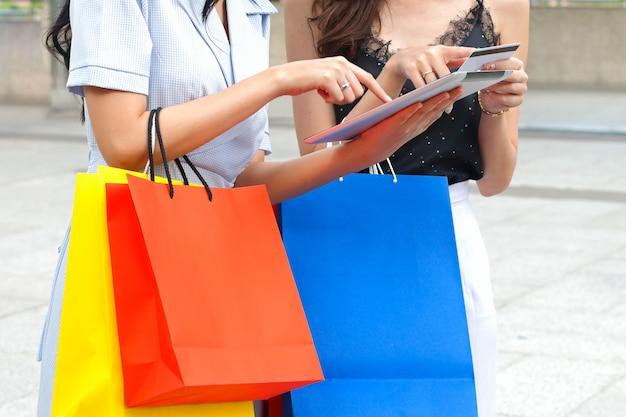 Vrouwen met boodschappentassen en tablet gebruiken