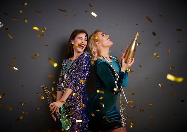 Vrouwen met champagne onder de douche van confetti