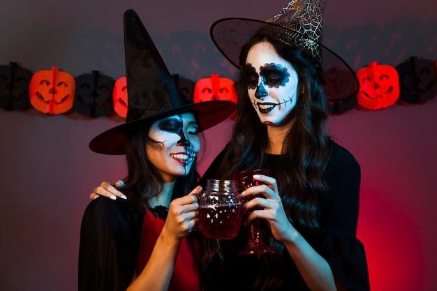 Vrouwen met drankjes gekleed als heksen