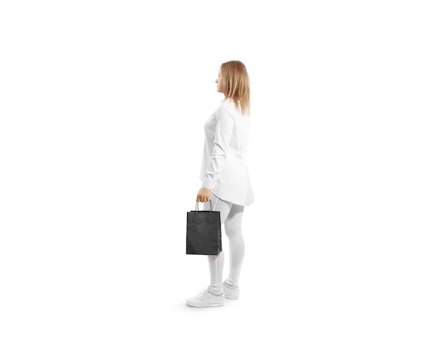 Vrouwen met een leeg zwart ambachtelijk papieren zakontwerp in de hand