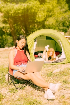 Vrouwen met gadgets rusten buitenshuis