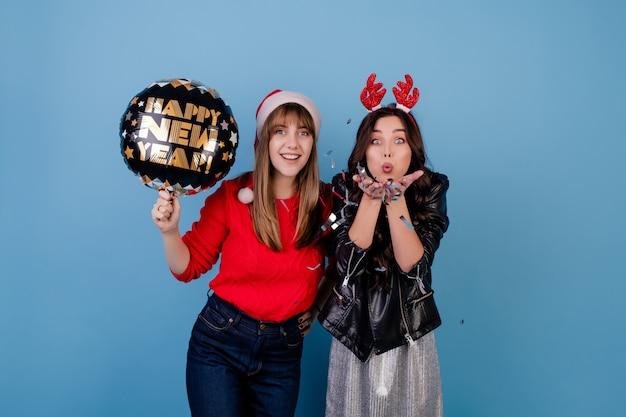 Vrouwen met gelukkige nieuwe jaarballon die kerstmishoed en de winterkleren dragen die over blauw worden geïsoleerd