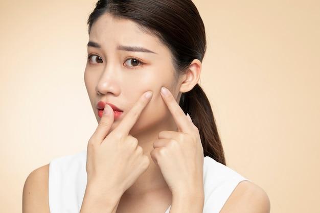 Vrouwen met gezichtshuidproblemen - ongelukkige jonge vrouwen die haar huid op een oranje achtergrond raken