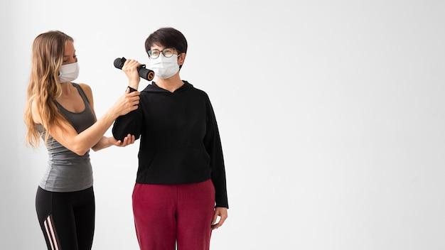 Vrouwen met gezichtsmaskers die met exemplaarruimte trainen