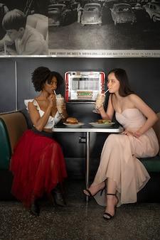 Vrouwen met hamburgers en drankjes aan tafel zitten