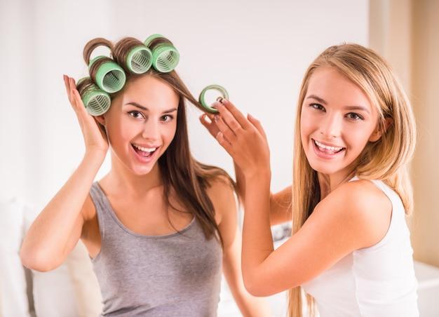 Vrouwen met kleurrijke haarrollen die bij bed en het glimlachen zitten.