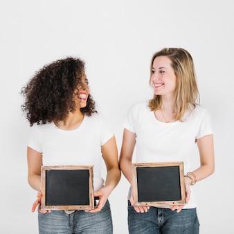 Vrouwen met krijtbord kijken elkaar aan