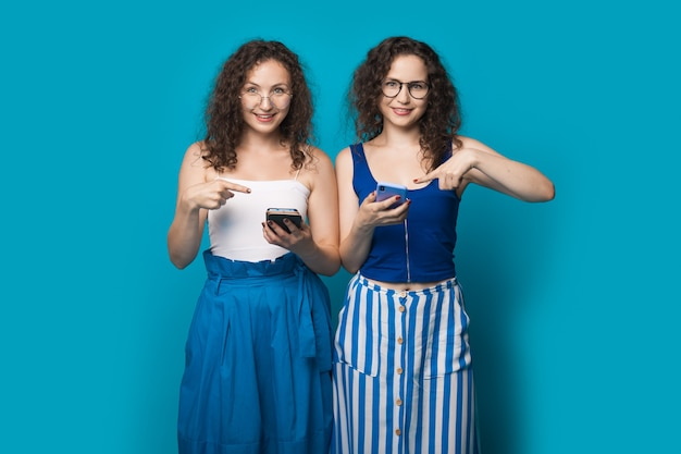 Vrouwen met krullend haar met bril wijzen naar hun telefoon