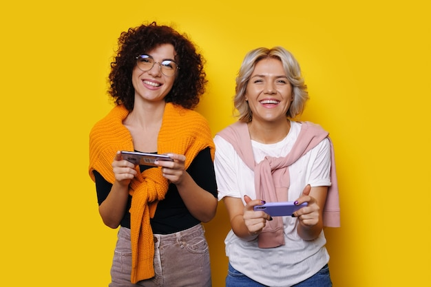 Vrouwen met krullend haar met een bril spelen met mobiel terwijl ze reclame maken voor een nieuw spel op een gele muur