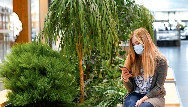 Vrouwen met maskers zitten in winkelcentrum, met telefoon, sociaal verspreid.