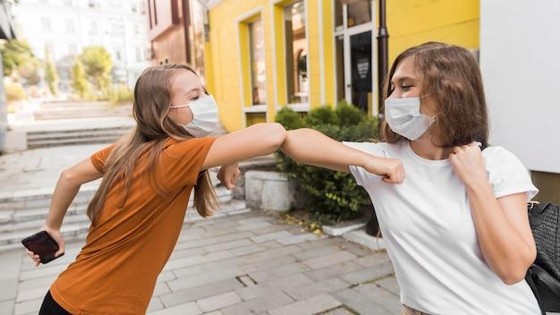 Vrouwen met medische maskers die ellebooggroet oefenen