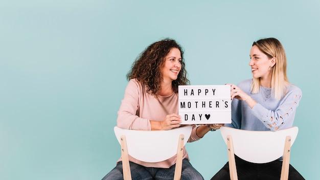 Vrouwen met moederdaggroeten op stoelen