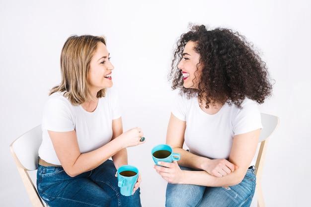 Vrouwen met mokken die gesprek hebben