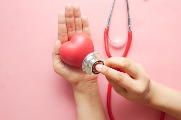 Vrouwen met rood hart en stethoscoop op roze