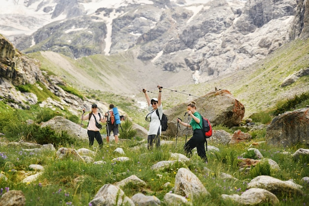 Vrouwen met rugzakken en scandinavische stokken beklimmen de bergen