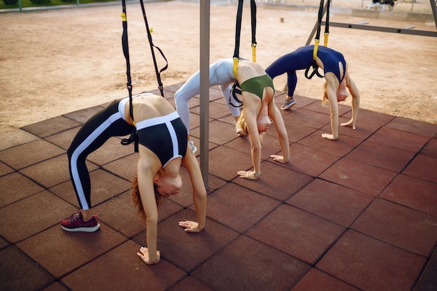 Vrouwen met slank lichaam fitte oefening met touwen op sportveld, groepstraining buitenshuis
