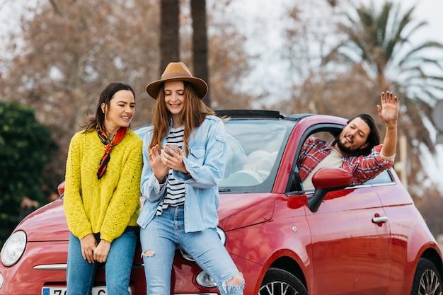 Vrouwen met smartphone dichtbij de mens die uit auto leunen