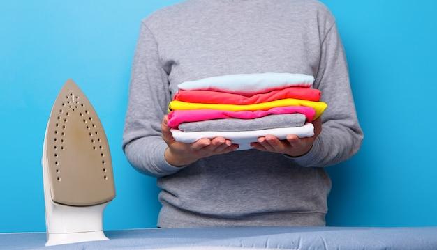 Vrouwen met strijkijzer en stapel kleren in haar handen. concept van huishoudelijk werk.