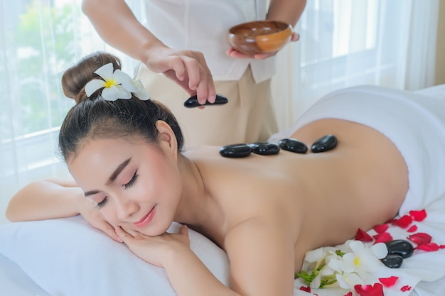 Vrouwen met therapeutische stenen op haar rug