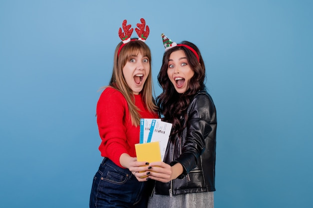 Vrouwen met vliegtuigtickets en paspoort die grappige die kerstmishoepels dragen over blauw worden geïsoleerd