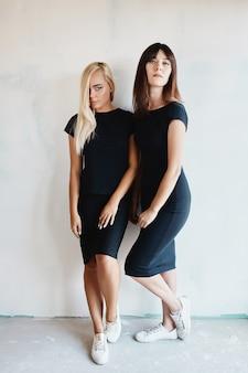 Vrouwen met zwarte jurk die zich voordeed op muur