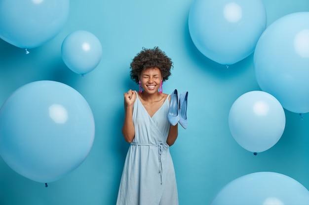 Vrouwen, mode, kledingconcept. blij dat jonge afro-amerikaanse vrouw balde vuist van vreugde, verheugt zich op nieuwe aankoop, koopt modieuze outfit en schoenen om zich te kleden voor speciale gelegenheden, blauwe kleur heerst