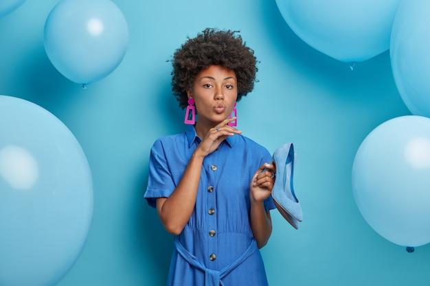 Vrouwen, mode, stijl, feesten concept. elegante ernstige vrouw in blauwe jurk, houdt schoenen met hoge hakken, jurken voor themafeest, klaar om uit te gaan, vormt tegen blauwe muur met helium ballonnen