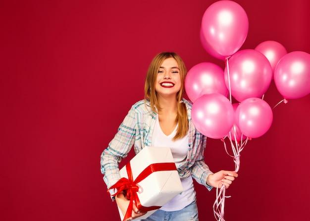Vrouwen model die en doos met gift huidige en roze luchtballons vieren houden