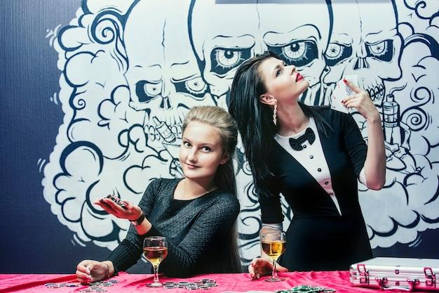 Vrouwen mooie jonge succesvolle gokken in casino's aan de tafel met de chips en alcohol