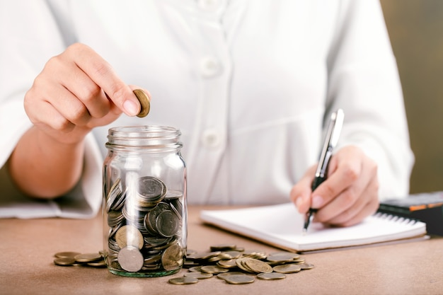 Vrouwen munt aanbrengend glazen fles spaarbank en een financiële boekhouding