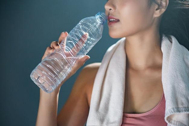 Vrouwen na het sporten drinken water uit flessen en zakdoeken in de sportschool.