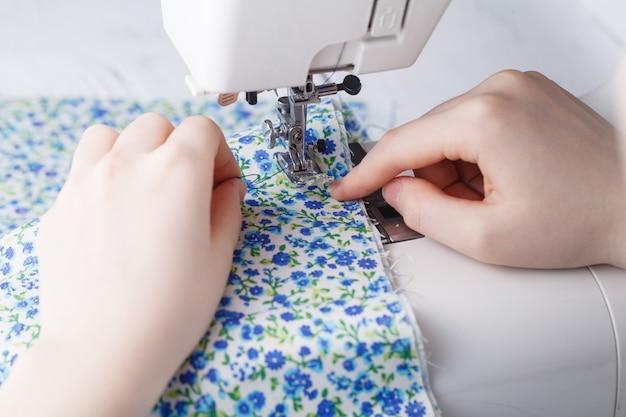 Vrouwen naaiende stof op naaimachine
