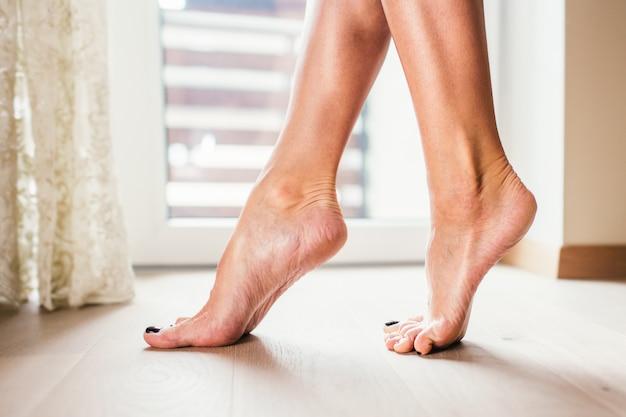 Vrouwen naakte voeten die op de vloer van het lighrparket dichtbij groot venster, close-up lopen.