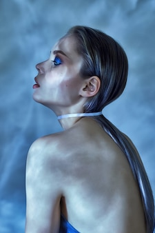 Vrouwen nat haar en het heldere make-up stellen dichtbij water