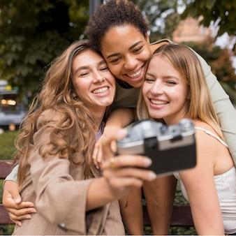 Vrouwen nemen een selfie met een retro camera