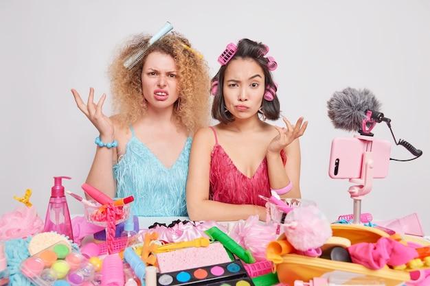 Vrouwen nemen online videovertaling op terwijl ze zich voorbereiden op een speciale gelegenheid kapsel maken verschillende cosmetische producten gebruiken de dag thuis doorbrengen tips voor dames geven