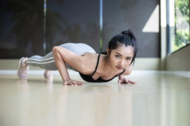 Vrouwen oefenen door de vloer in de sportschool te duwen