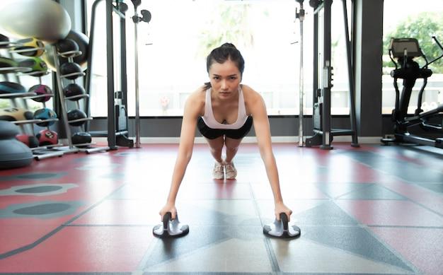 Vrouwen oefenen door de vloer te duwen met fitness push up stands in de sportschool